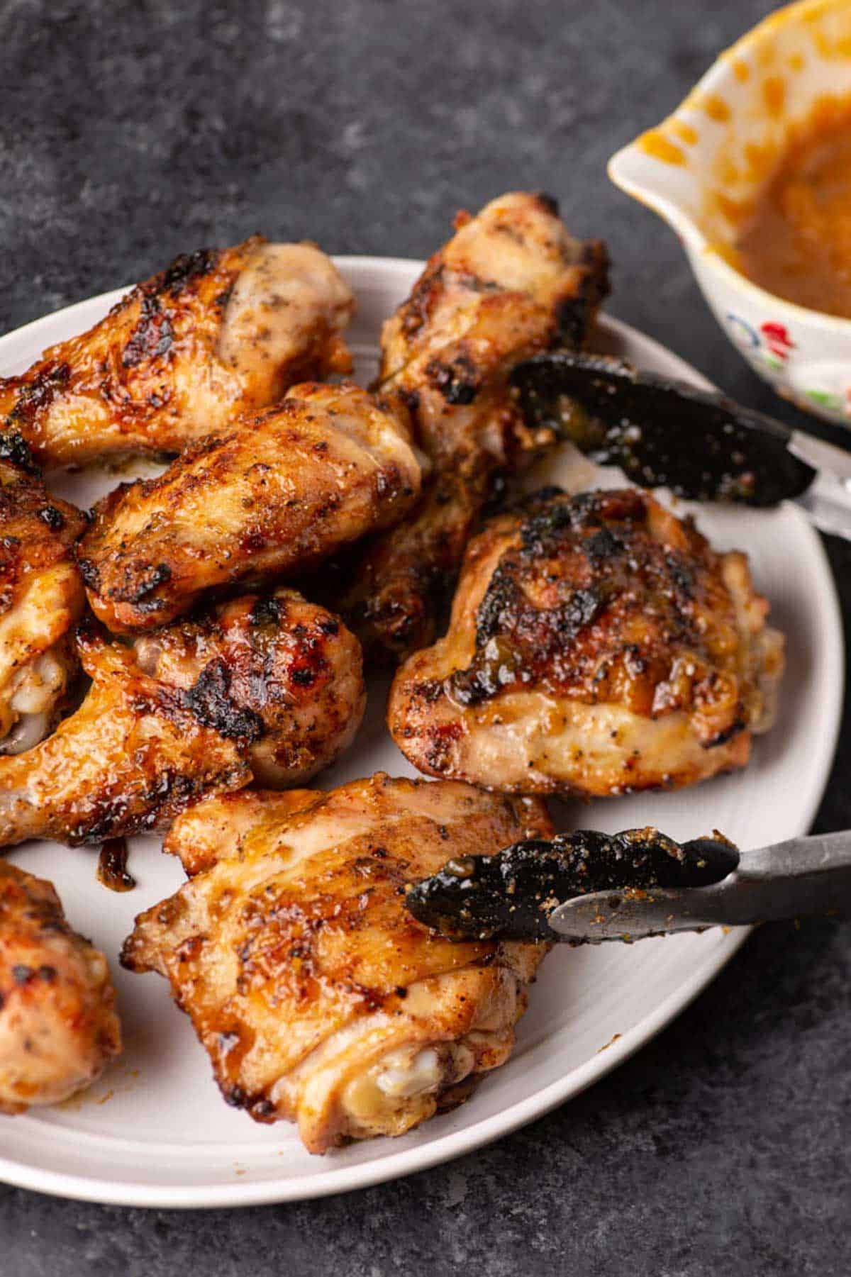 A white platter full of grilled chicken drumsticks and thighs.