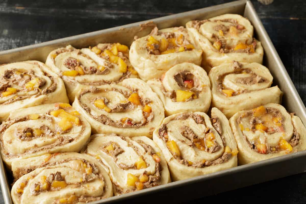 Cinnamon rolls in a baking pan before they have been put into the oven.