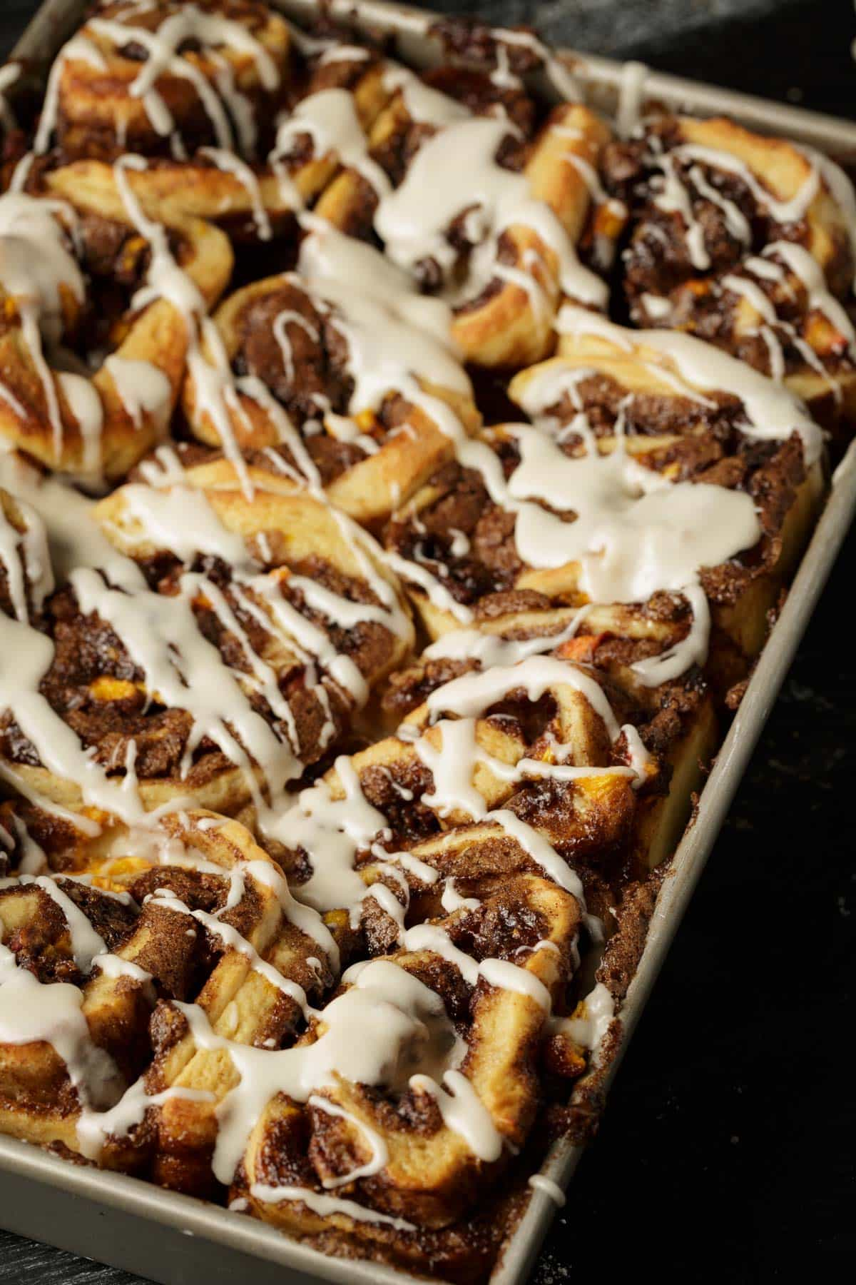 A baking pan of homemade cinnamon rolls with a bourbon glaze drizzled over the top.