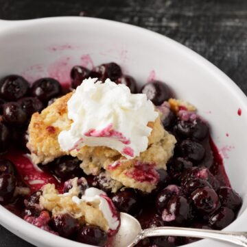 A ramekin filled with Southern blueberry cobbler with a spoon