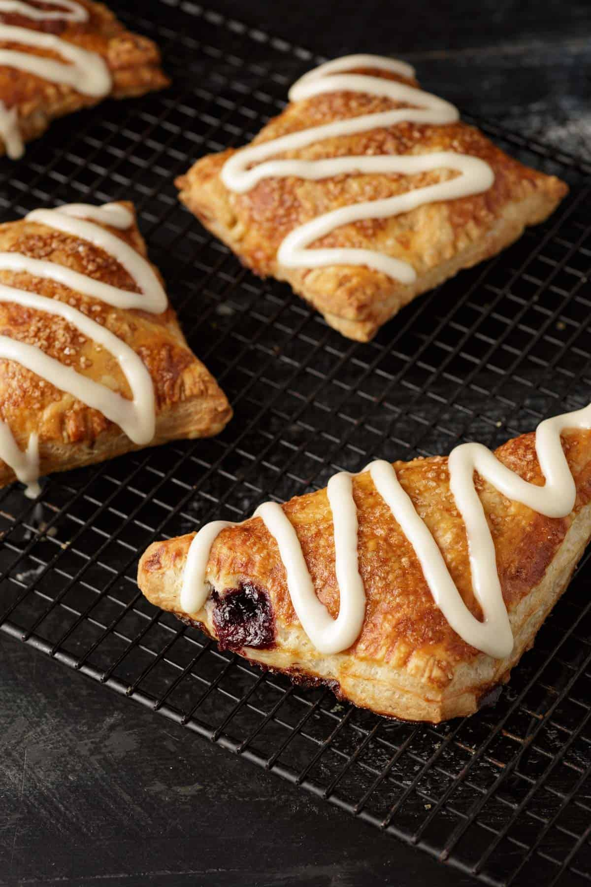 Frosted cherry hand pies on a black rack