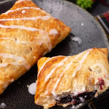 two cherry hand pies on a plate with a glaze drizzled on them