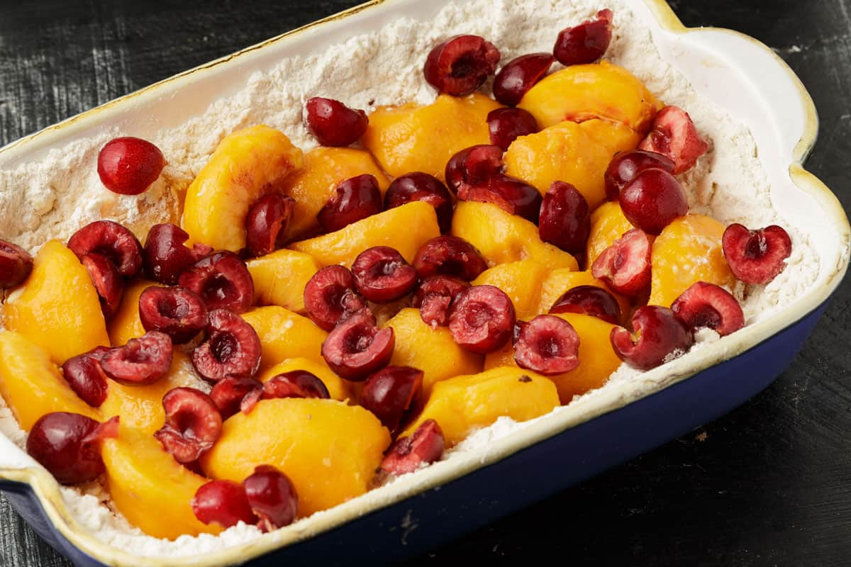 A baking dish of fruit on top of a cake layer.