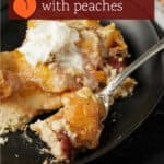 A fork full of peach kuchen with cherries.