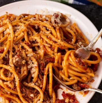 Pasta with Sunday gravy being twirled with two forks