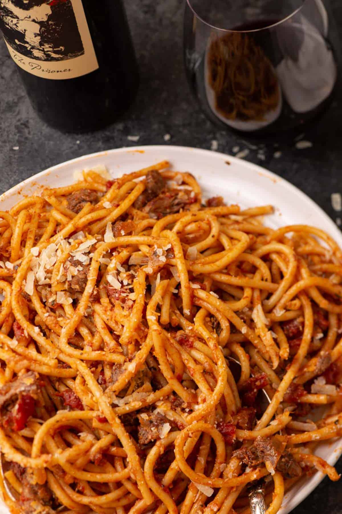 A platter of pasta with a bottle of wine