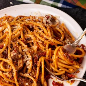 A plate of pasta with Sunday sauce being swirled