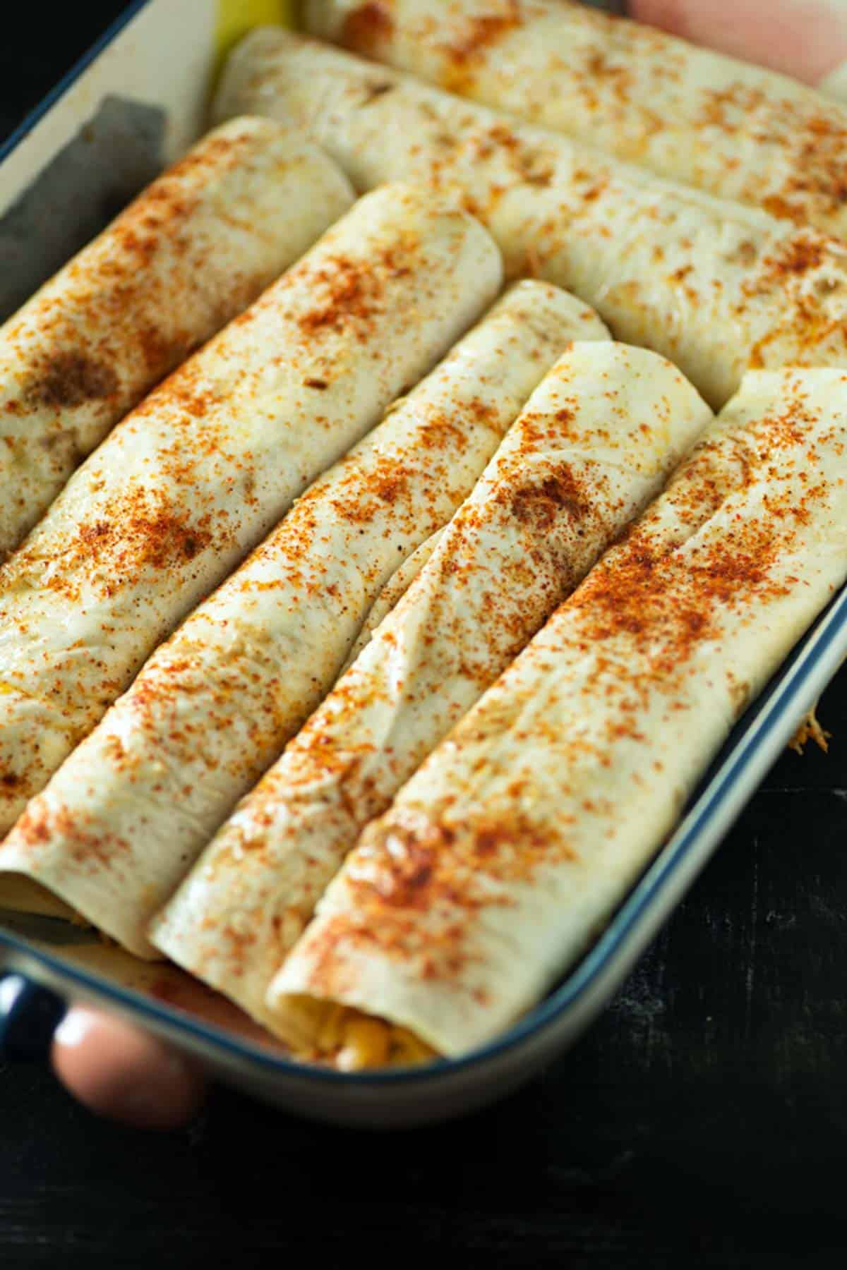 Tortillas filled with chicken and cheese in a baking dish.