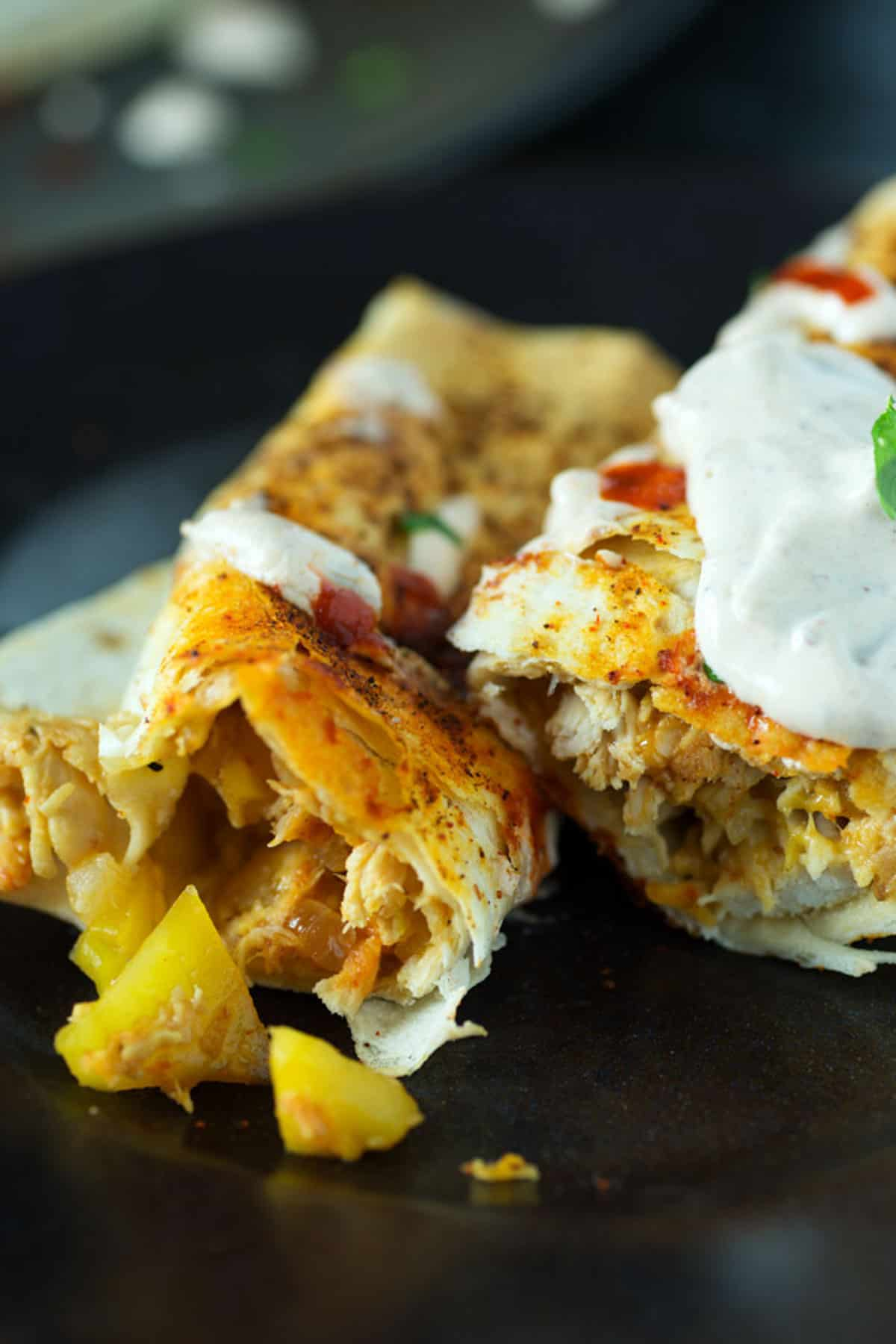 Two peach and chicken taquitos on a plate.