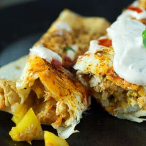 A peach and chicken baked taquitos with yogurt sauce.