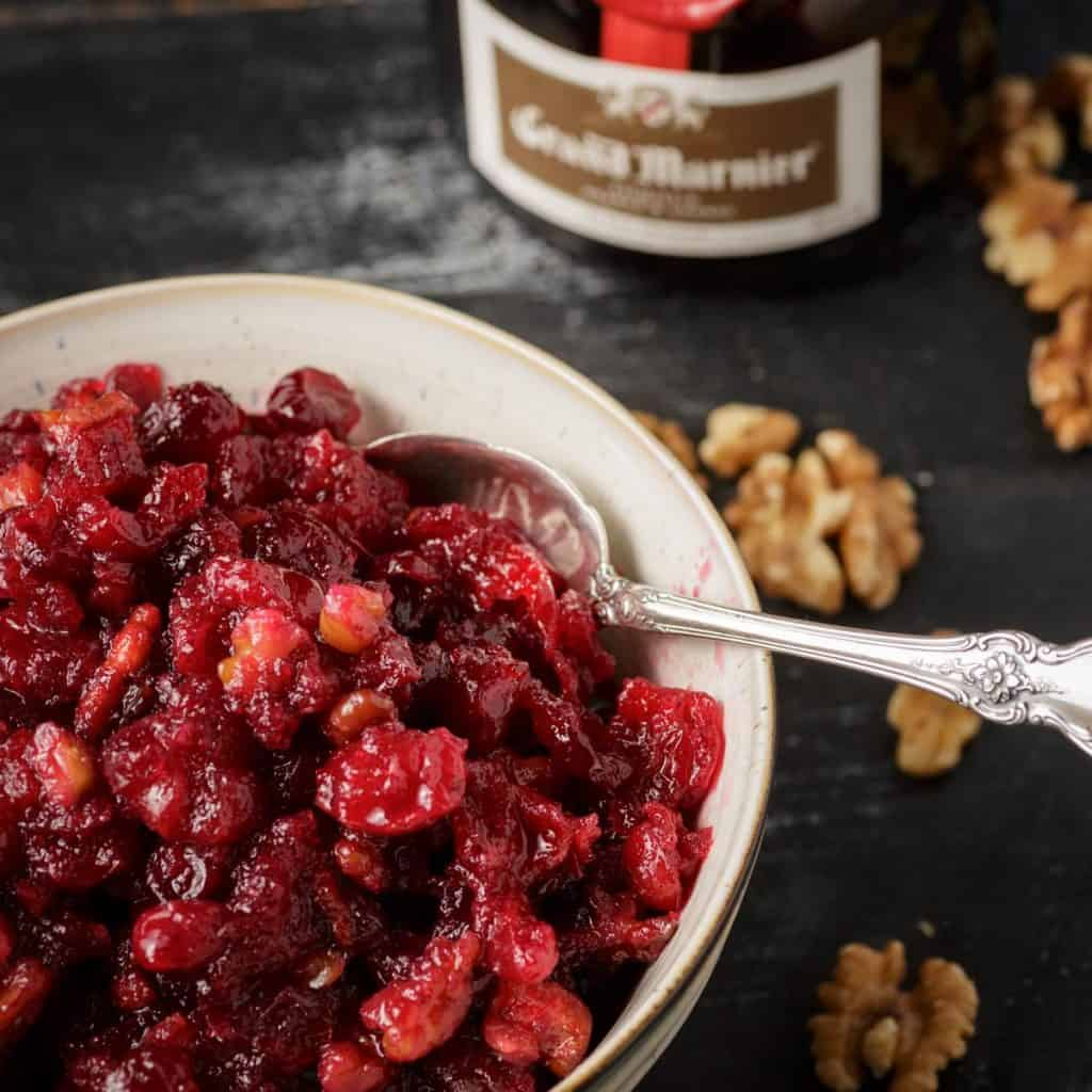 A bowl of cranberry sauce with a bottle of grand marnier