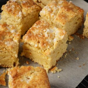 A batch of cornbread biscuits cut on parchment papeer