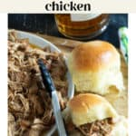 Slow Cooker Bourbon Pulled Chicken in a bowl and two sandwiches next to it and a bottle of bourbon in the background.