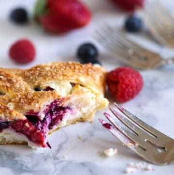 A slice of berry braid with a bite removed.