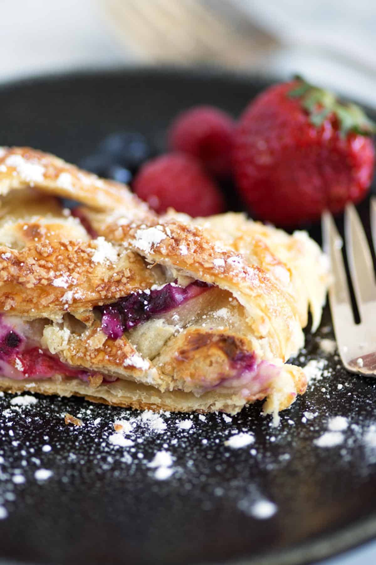 A slice of berry pastry braid with powdered sugar.