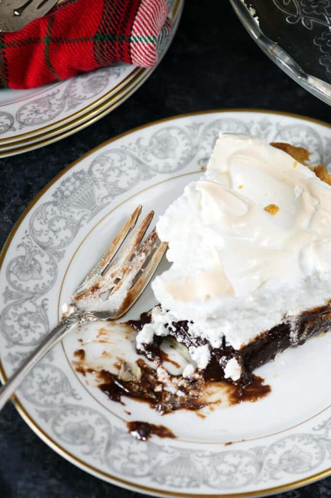 A slice of chocolate pie with a bite taken out of it.
