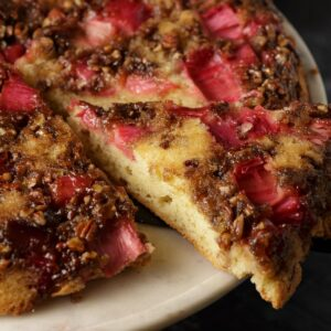 A slice of rhubarb upside down cake on a marble platter