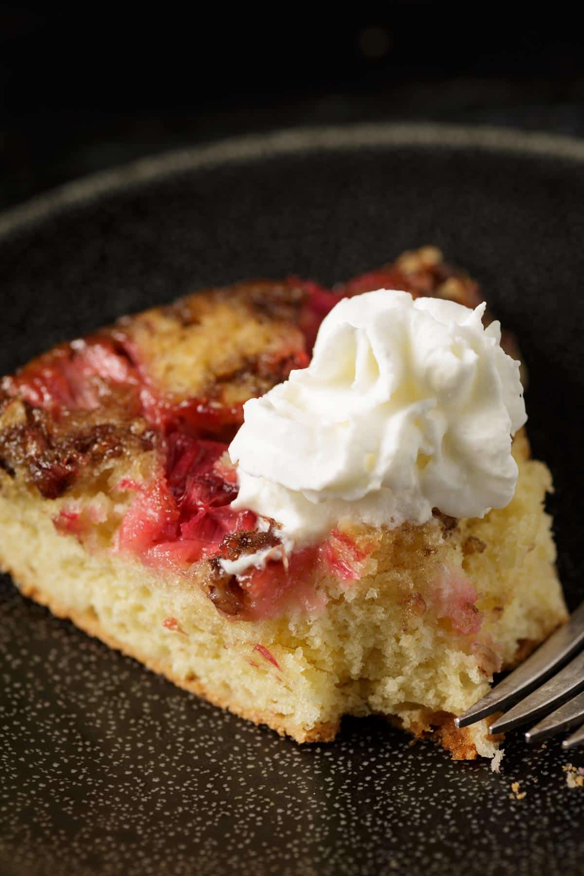 A slice of rhubarb upside down cake with whipped cream on top