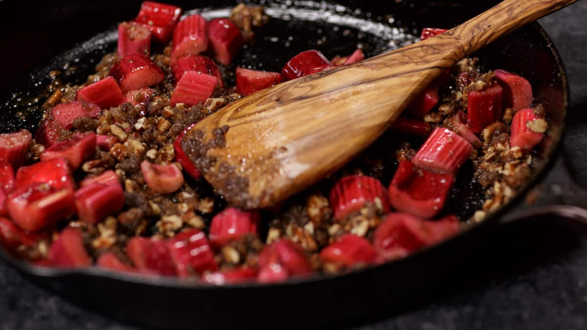 Rhubarb and brown sugar in an iron skillet with a wooden spoon
