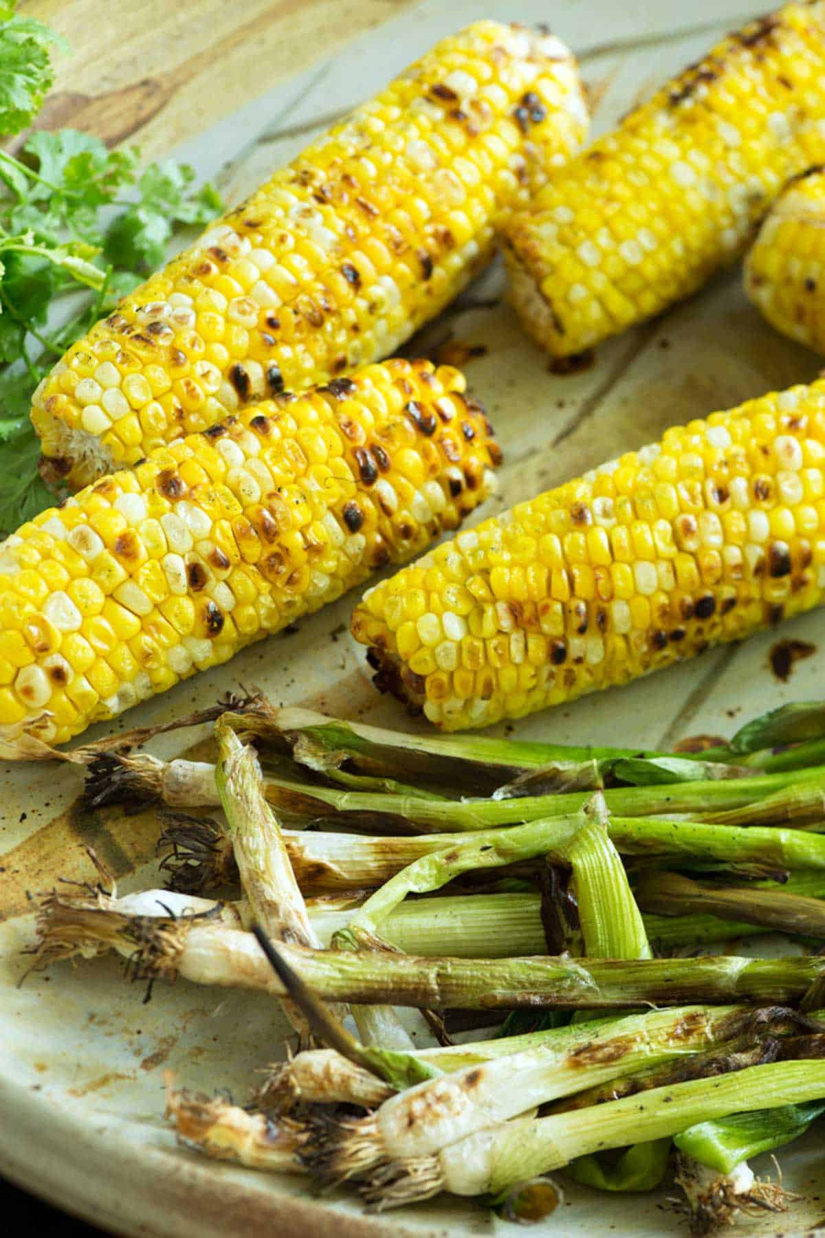 Grilled corn and green onions on a platter