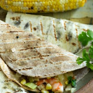 A grilled tortilla stuffed with shrimp and corn