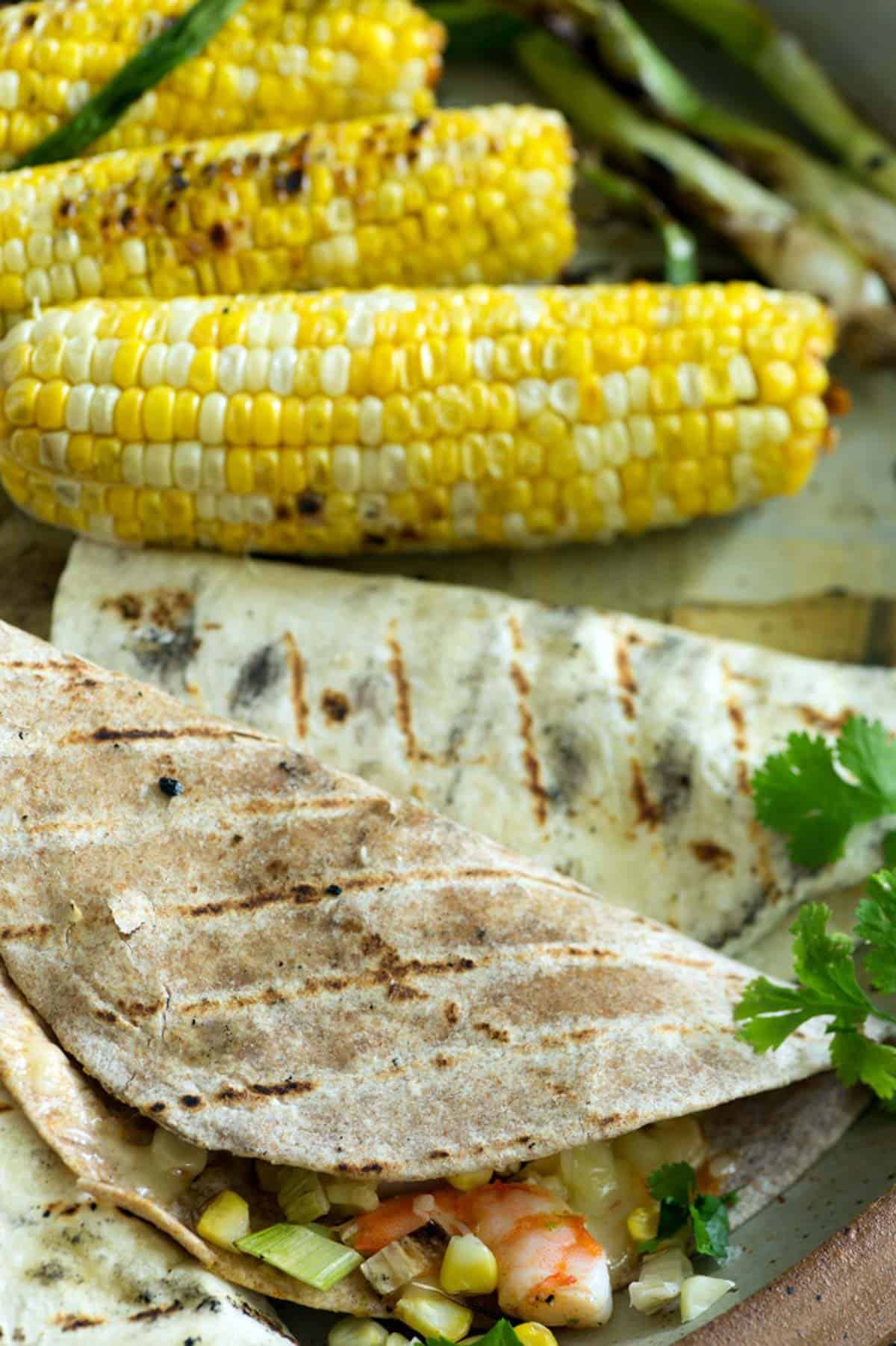 A platter with two shrimp quesadillas with grilled corn in the background.