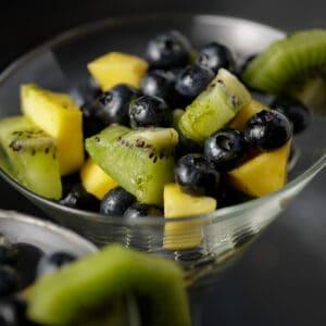 Blueberry fruit salad in martini glasses.