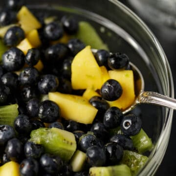 A glass bowl of tequila blueberry salad with a spoon of mango slices.