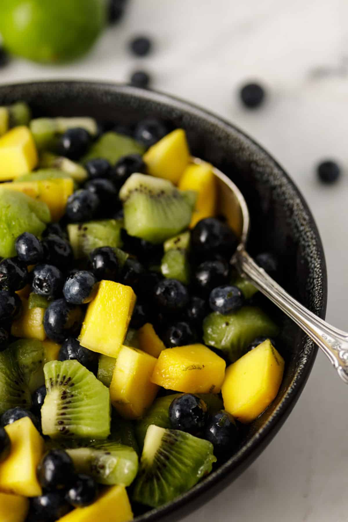 A fresh summer salad with blueberries and mango in a black bowl.