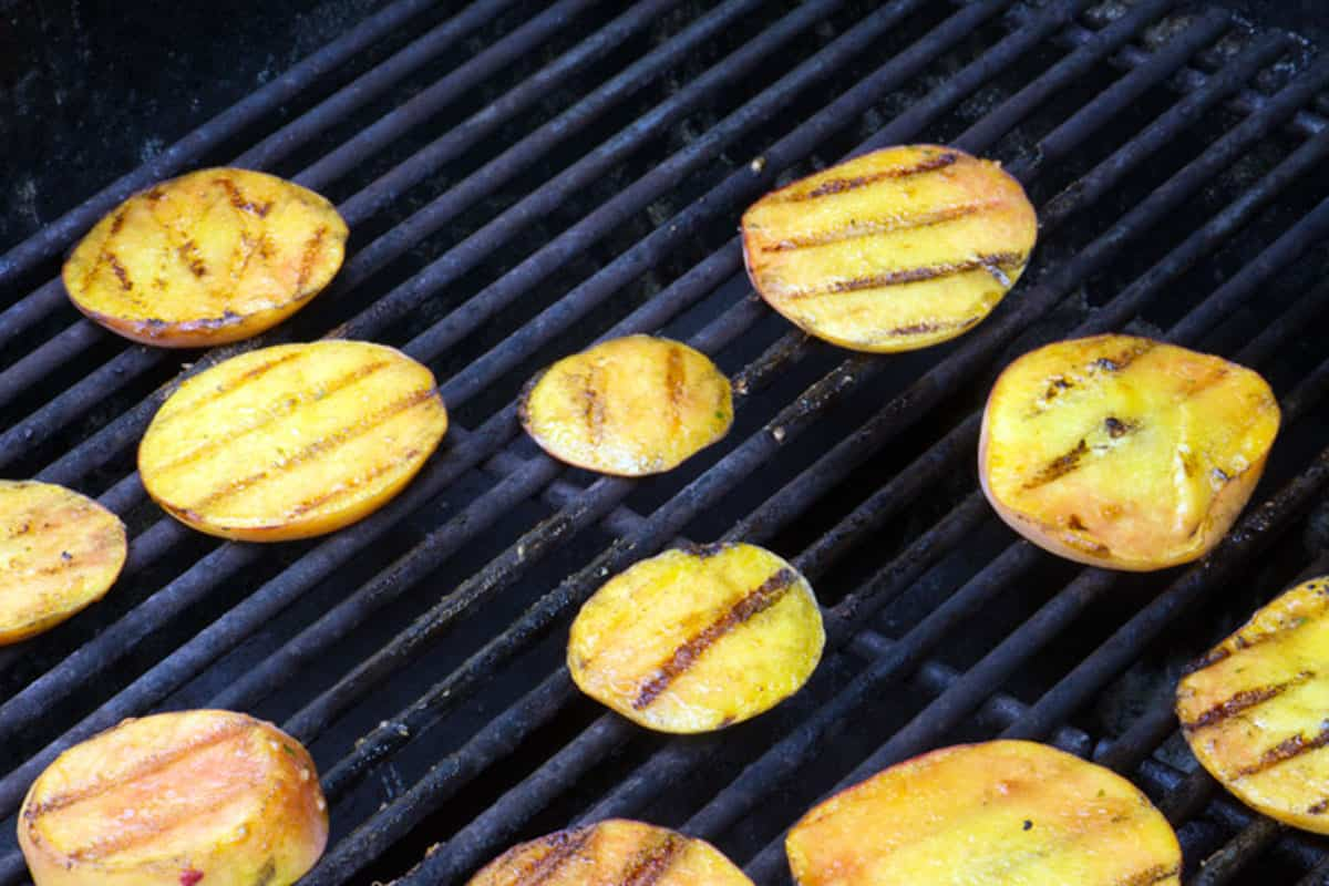 Sliced peaches on a grill.
