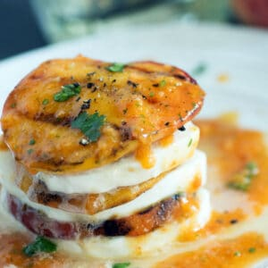 Grilled peach slices stacked with mozzarella with a peach puree over the top.