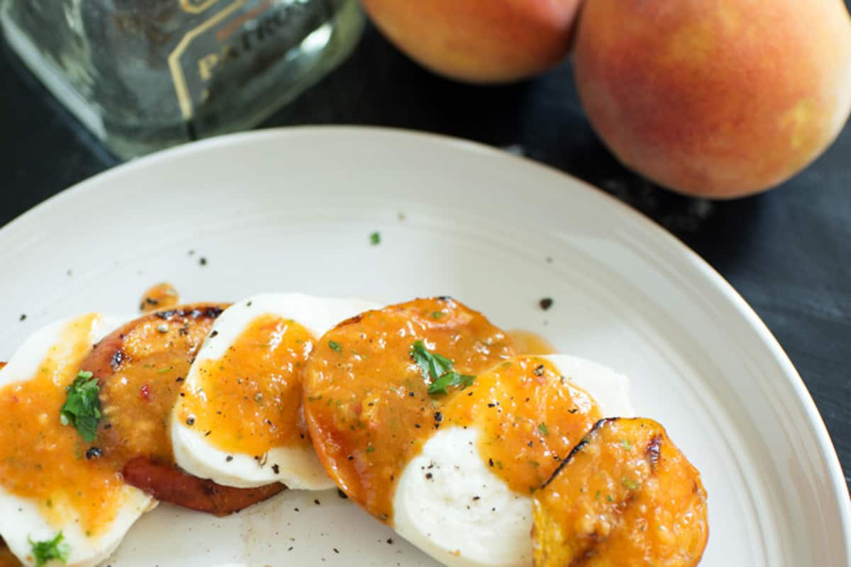 Slices of mozzarella and grilled peaches with sauce poured over them.