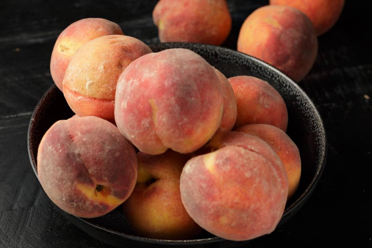 A black bowl full of peaches.
