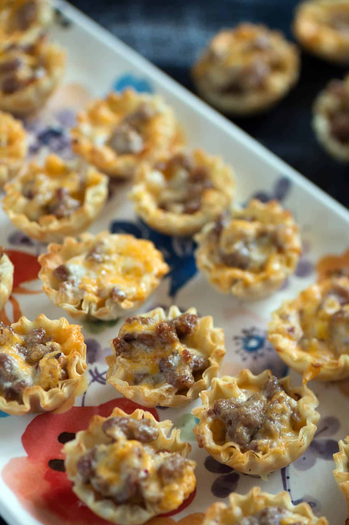 A platter of phyllo cups with sausage.