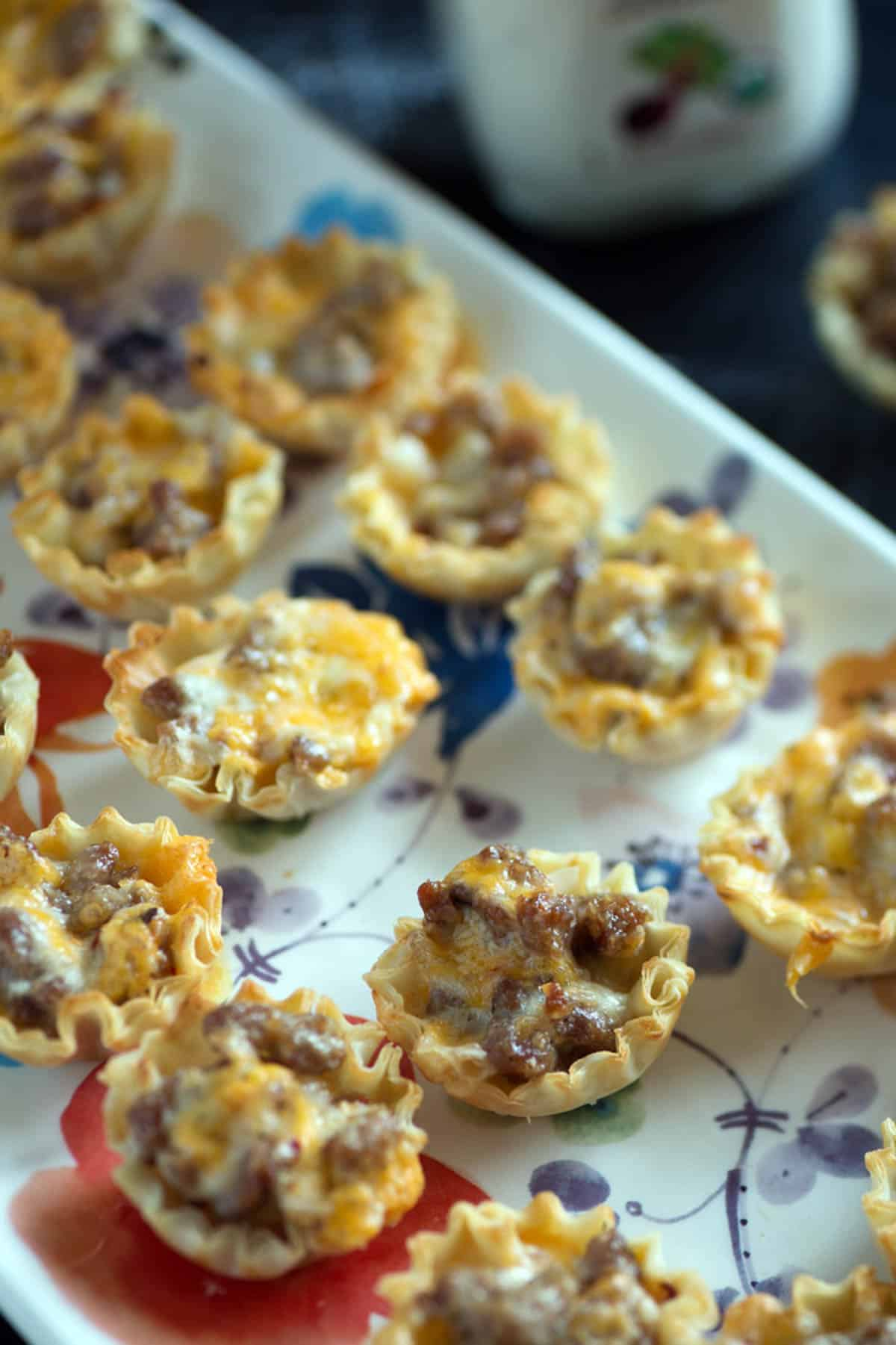 Appetizer sausage cups on a platter.