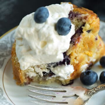 A fork on a plate with a slice of blueberry and peach cake