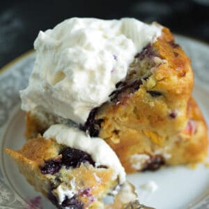 A fork full of peach cake with whipped cream.