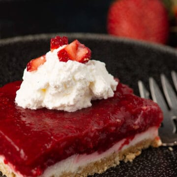 A serving of strawberry pretzel salad with topped with whipped cream