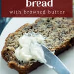 A slice of banana bread with a knife spreading butter across it/
