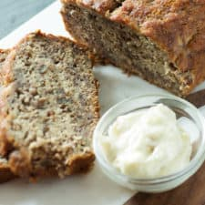 A loaf of Browned Butter Banana Bread with a bowl of vanilla butter