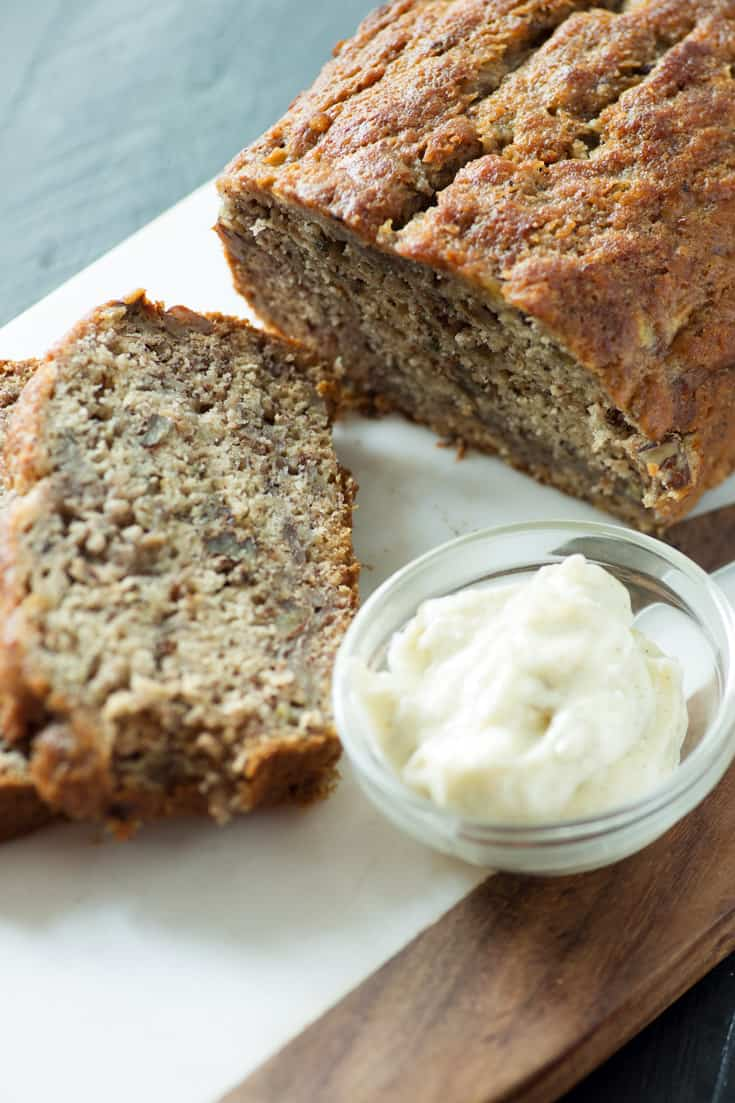A loaf of Brown Butter Banana Bread with a bowl of vanilla butter