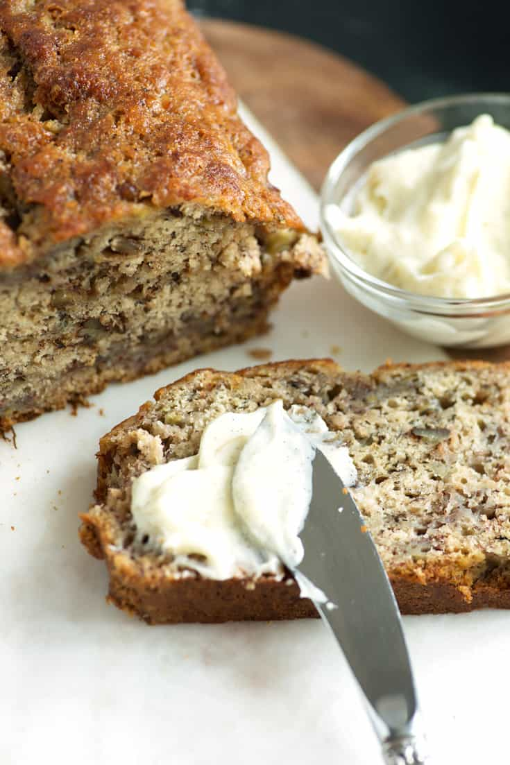 A slice of browned butter banana bread with vanilla butter on a knife
