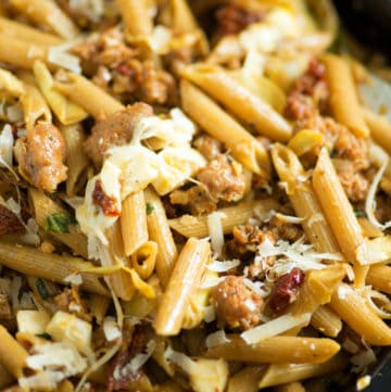A skillet of penne with artichokes and Italian sausage