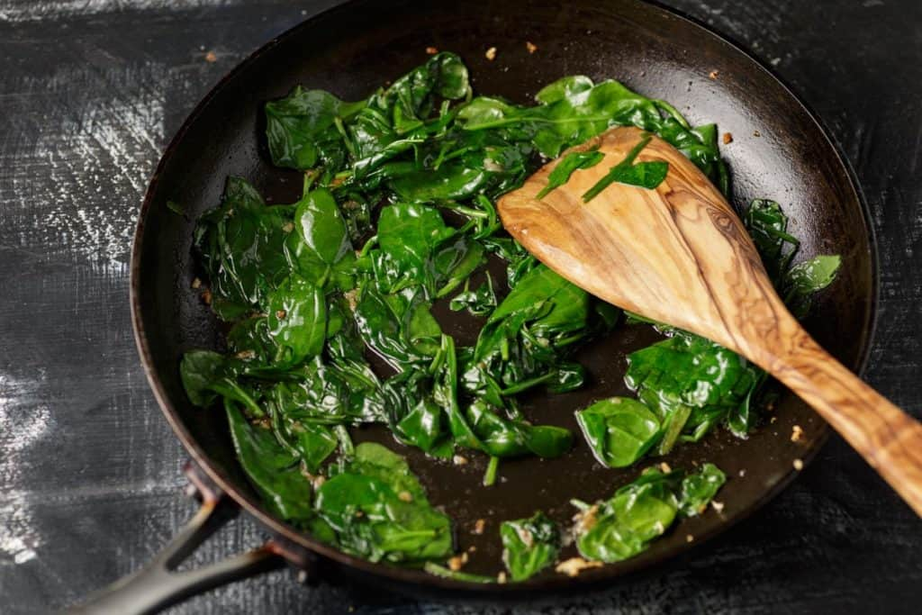 A skillet of spinach and garlic with a wooden spoon