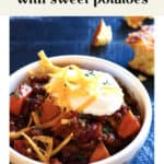 Apple Cider Chili with Sweet Potatoes in a bowl with sour cream and cheese on top.