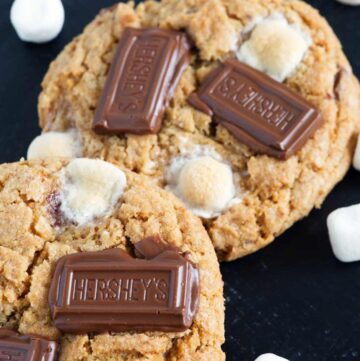 Two S'more cookies with loose marshmallows around them.
