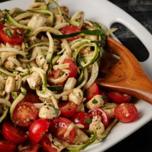 Zucchini noodles with cherry tomatoes on a white platter with a wooden spoon
