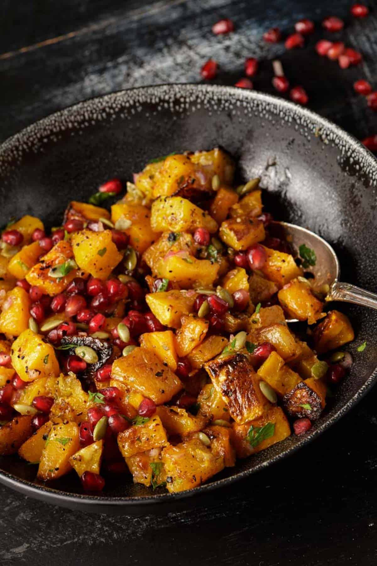 A black bowl with butternut squash and pomegranates.