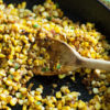 Charred Corn in a skillet with a wooden spoon
