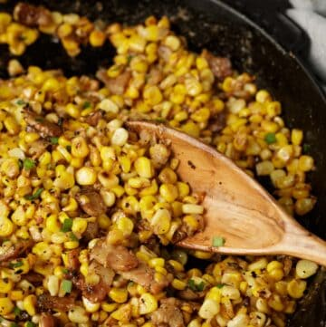 A skillet of charred corn with a wooden spoon.